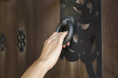 Ręka trzyma drzwiowego knocker Fotografia Stock