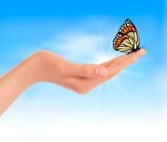 Ręka trzyma motyla przeciw niebieskiemu niebu. Fotografia Royalty Free