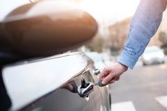 Ręka trzyma samochodowego klucz i otwiera samochodowego drzwi Zdjęcia Royalty Free