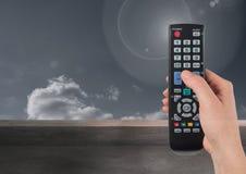 Ręka trzyma tv pilot do tv przed chmurami Obraz Royalty Free
