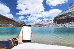 Ręka w modnisia koszulowego mienia pustym smartphone z zielonym jeziorem Zdjęcia Stock