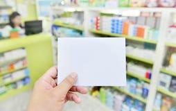 Ręka z nutowym ochraniaczem na zamazanym w apteka sklepie Obrazy Royalty Free