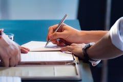 Ręka z pióra podpisywania dokumentem, zamyka up Obrazy Stock