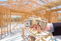 Ręka Z stertami gotówka Na miejsca Inside Nowej Domowej budowie Fr Zdjęcie Royalty Free
