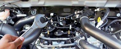 Ręka z wyrwaniem sprawdza samochodowego silnika Obraz Stock