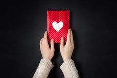 Ręki mienia czerwony prezent na czerni Zdjęcie Royalty Free