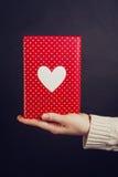 Ręki mienia czerwony prezent na czerni Zdjęcia Stock