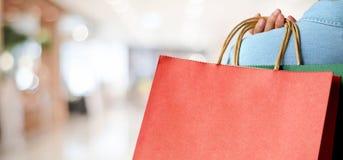 Ręki mienia czerwony torba na zakupy na plama sklepu tle, sztandar w Obrazy Stock