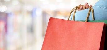 Ręki mienia czerwony torba na zakupy na plama sklepu tle, sztandar w Obraz Royalty Free