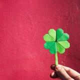 Ręki mienia papieru origami zieleni shamrock na menchiach Obrazy Stock
