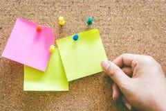 Ręki mienia przypomnienia kleista notatka na korek desce Zdjęcia Stock