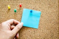 Ręki mienia przypomnienia kleista notatka na korek desce Zdjęcie Stock