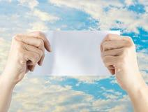 Ręki mienia pusty papier z niebieskim niebem Obraz Royalty Free