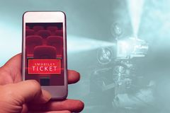 Ręki mienia smartphone dla zarezewowanego filmu bileta Zdjęcie Stock