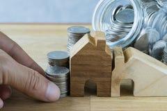 Ręki mienia sterta monety z drewnianym miniatura domem jak finan Zdjęcia Royalty Free