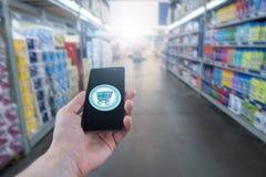 Ręki mienia telefon komórkowy na supermarket plamy tle Zakupy kosz na telefonu komórkowego ekranie zdjęcia royalty free