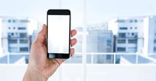 Ręki mienia telefon z miasta okno Zdjęcia Royalty Free