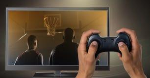 Ręki trzyma hazardu kontrolera z graczami koszykówki na telewizi Obraz Stock