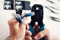 Ręki trzyma kable i forceps dla crimping prymki Fotografia Stock