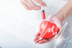 Ręki trzyma plastikowej strzykawki medycznego zastrzyka czerwony serce Fotografia Stock