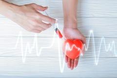 Ręki trzyma plastikowej strzykawki medycznego zastrzyka czerwony serce Obrazy Stock