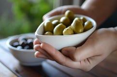 Ręki trzyma zielone i czarne oliwki w ceramicznych garnkach Zdjęcie Stock