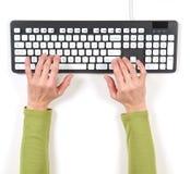 Ręki w zielonej kurtce i popielatej klawiaturze Fotografia Royalty Free