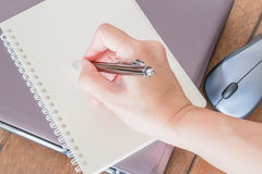 Ręki writing na nutowym papierze przy miejscem pracy Zdjęcia Royalty Free