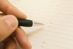 Ręki writing telefonu komórkowego liczba w biznesowej agendzie Obrazy Royalty Free