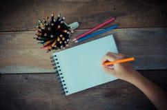 Ręki writing w otwartym notatniku na stole Zdjęcie Stock