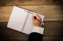 Ręki writing w otwartym notatniku na stole Fotografia Stock
