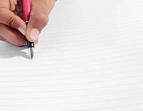 Ręki writing z piórem na liniowa papierze Obrazy Royalty Free