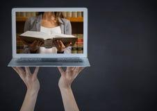 Ręki z laptopem pokazuje kobiety czytanie przeciw chalkboard Zdjęcia Stock