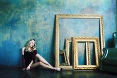 R?knar samman den b?rande kronan f?r den unga blonda kvinnan i felik lyxig inre med tomma antika ramar rikedombegrepp arkivfoto