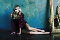 R?knar samman den b?rande kronan f?r den unga blonda kvinnan i felik lyxig inre med tomma antika ramar rikedombegrepp royaltyfri bild