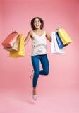r La mujer encantada con los bolsos salta para arriba con placer Imagenes de archivo