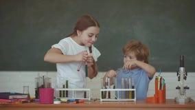 r Los niños y el profesor está aprendiendo en clase en el fondo de la pizarra Lecciones de la qu?mica de la escuela almacen de video
