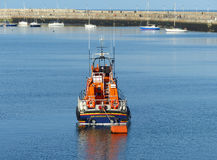 The R.N.L.I. lifeboat moored in the calm waters beside the famous Victorian East Pier of Dunloaghaire harbor. The R.N.L.I. lifeboat moored in the calm blue Stock Photos