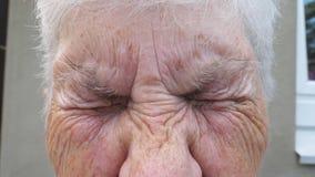 关闭调查与哀伤的视域的照相机的老祖母的起皱纹的面孔 r 股票录像