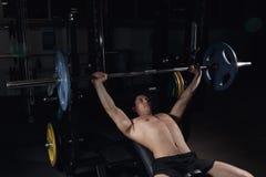 r O homem atlético que bombeia acima muscles na imprensa de banco imagem de stock royalty free