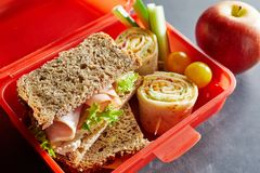 R plastic kids lunch box with healthy food. Colorful red plastic kids lunch box filled with healthy food including fresh vegetables, a wholewheat ham sandwich stock photos