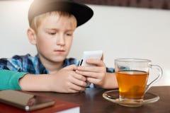 r Ragazzo bello in camicia e cappuccio controllati facendo uso dell'ubicazione del telefono cellulare in caffè con una tazza di t fotografie stock libere da diritti