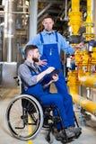 R?relsehindrad arbetare i rullstol i fabrik och kollega arkivfoto