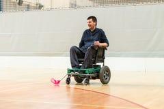 R?relsehindrad man p? en elektrisk rullstol som spelar sportar, powerchairhockey IWAS - Internationell rullstol och amputerad arkivbild