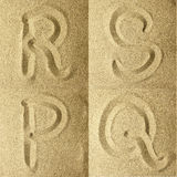 R s t u handwritten in the sand. Golden colors Stock Photos