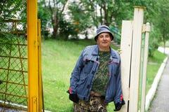 R?ssia Bashkortostan, vila de Abzakovo - julho, 8, 2019 Um jardineiro-construtor amável cumprimenta convidados na cerca de sua ca foto de stock royalty free