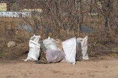 R?ssia, Kazan - 20 de abril de 2019: Sacos de lixo no banco de rio imagem de stock royalty free