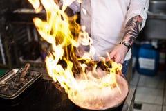 R?ssia, St Petersburg, 03 17 2019 - o cozinheiro chefe est? fazendo o flambe em uma cozinha do restaurante, fundo escuro imagens de stock royalty free