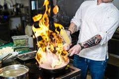 R?ssia, St Petersburg, 03 17 2019 - o cozinheiro chefe est? fazendo o flambe em uma cozinha do restaurante, fundo escuro fotos de stock royalty free