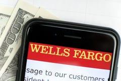 R?SSIA, ST PETERSBURGO, o 4 de abril de 2019: Logo Wells Fargo Co nas notas de dólar de encontro do smartphone foto de stock royalty free